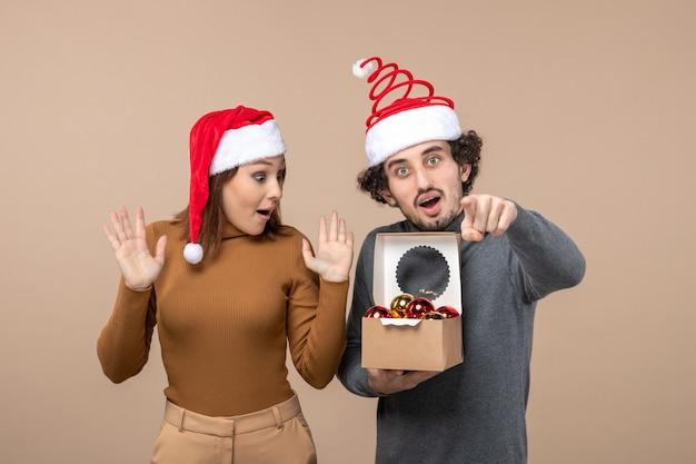 Festliche stimmung mit aufgeregtem coolem paar, das roten weihnachtsmannhut-kerl trägt, der boxon graues filmmaterial öffnet