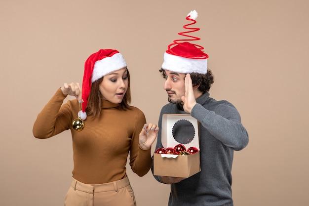 Festliche stimmung mit aufgeregtem lustigem coolem paar, das rote weihnachtsmannhüte auf grauem filmmaterial trägt
