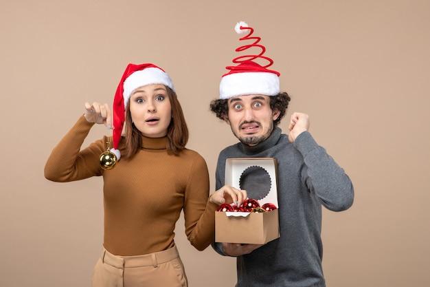 Festliche stimmung mit aufgeregtem reizendem coolem paar, das rote weihnachtsmannhüte auf grauem filmmaterial trägt