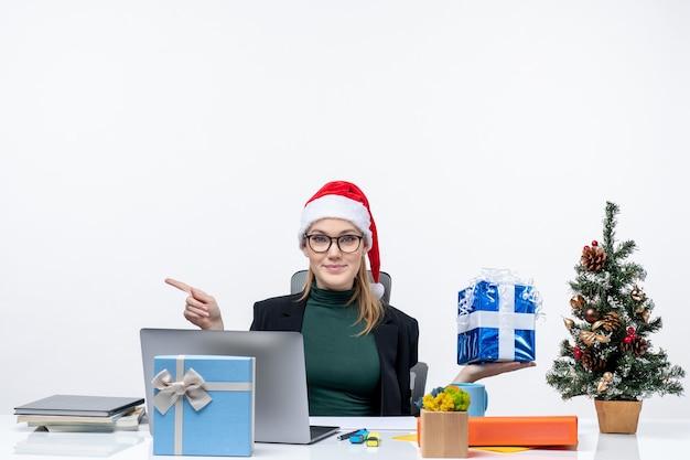 Festliche stimmung mit neugieriger überraschender lächelnder junger frau mit weihnachtsmannhut, der brillen trägt, die an einem tisch sitzen, der weihnachtsgeschenk zeigt, das etwas auf der rechten seite zeigt