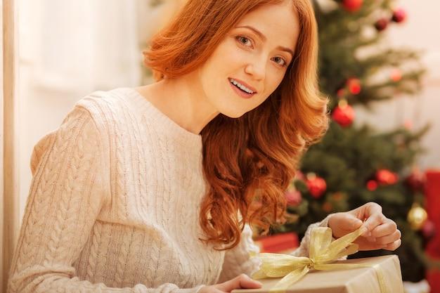 Festliche stimmung. strahlende reife frau, die zu hause sitzt und ein wunderschön verpacktes geschenk an einem weihnachtsmorgen öffnet.