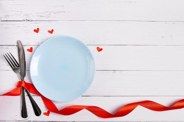 Festliche tabelleneinstellung für valentinstag mit blauer leerer platte auf weißem hölzernem hintergrund