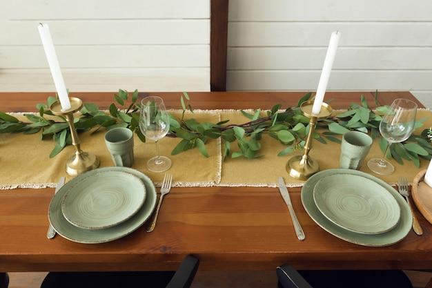 Festliche tischdekoration, holztisch mit grünen tellern und frühlingskräutern. hochwertiges foto
