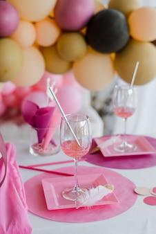 Festliche tischdekoration in rosa farben, weiße teller, gläser mit cocktailsticks. bunte luftballondekoration. geburtstag, babyparty oder mädchenparty.