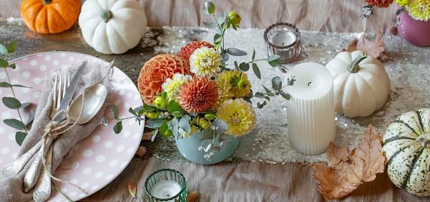 Festliche tischdekoration mit kürbiskerzen und chrysanthemenblüten