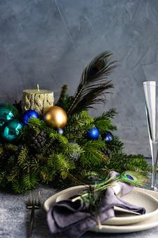 Festliche tischdekoration mit pfauenfeder zum weihnachtsessen auf steinbrett verziert