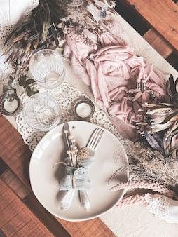 Festliche tischdekoration mit zweigen getrockneter blumen und dekorativen elementen.