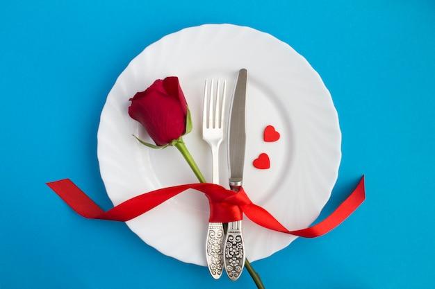 Festliche tischdekoration. rote rose, gabel und messer auf dem weißen teller in der mitte der blauen oberfläche. draufsicht. speicherplatz kopieren.