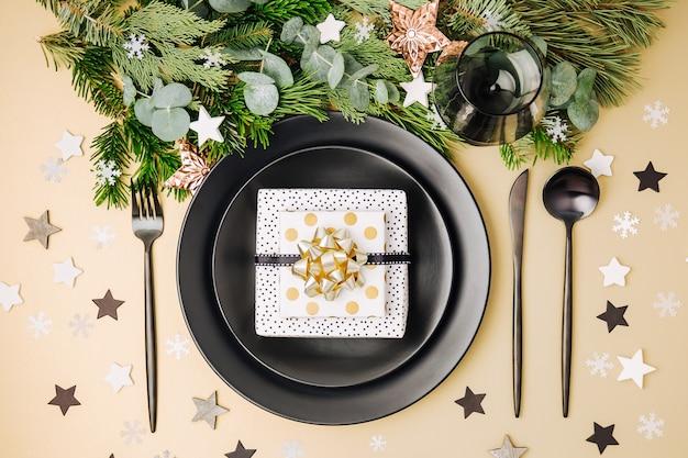 Festliche tischdekoration. schwarze teller mit geschenk- und weihnachtsschmuck mit tannenzweig.