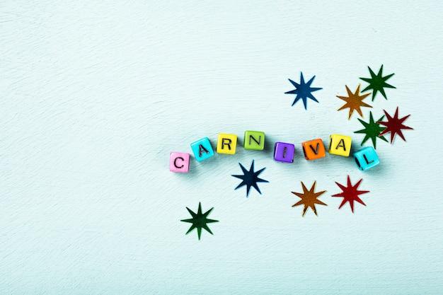 Festliche türkisfarbene oberfläche mit bunten würfeln mit textkarneval. grußkartenkonzept für karneval und party. kopierraum, draufsicht, flache lage