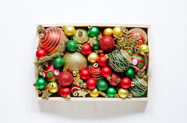 Festliche weihnachtsaccessoires in einem holztablett auf weißem holzhintergrund. aufnahmen von oben.