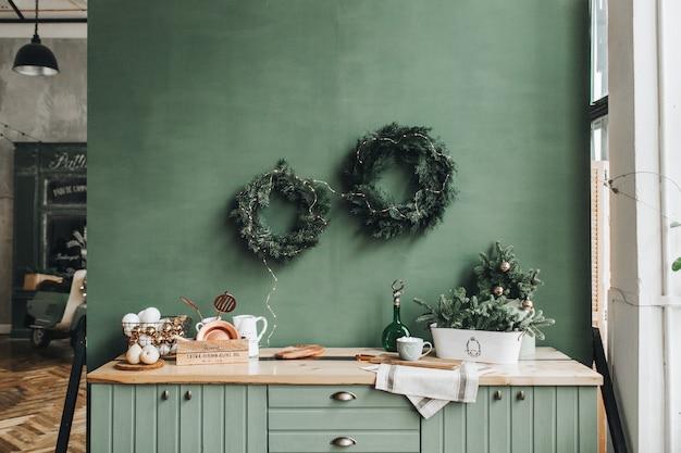 Festliche weihnachtsdekoration in der küche mit handgefertigtem kranz aus tannenzweigen, gold und weißem spielzeug