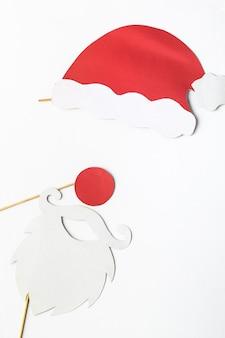 Festliche weihnachtsdekoration weiße bartbrille und roter weihnachtsmannhut auf stöcken