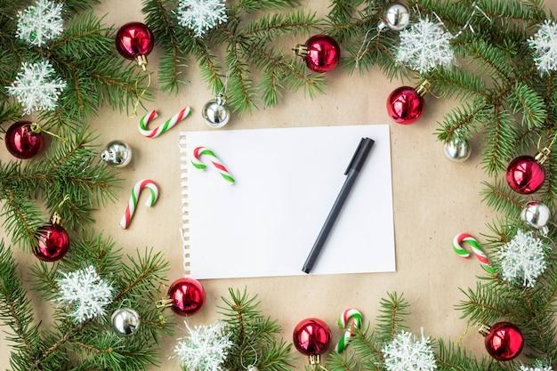 Festliche weihnachtsgrenze mit den roten und silbernen bällen auf tannenzweigen und schneeflocken auf rustikalem beige hintergrund