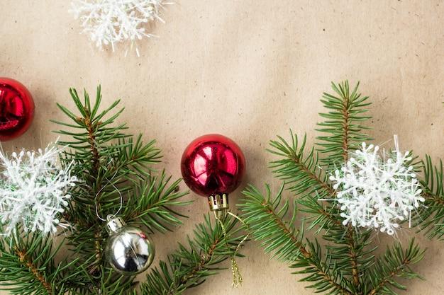 Festliche weihnachtsgrenze mit den roten und silbernen bällen auf tannenzweigen und schneeflocken