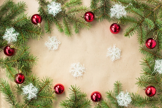 Festliche weihnachtsgrenze mit roten bällen auf tannenzweigen und schneeflocken auf rustikalem beige hintergrund