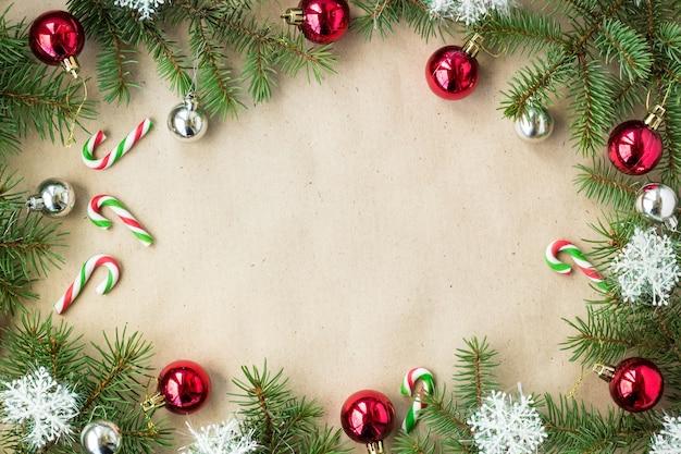 Festliche weihnachtsgrenze mit roten und silbernen kugeln auf tannenzweigen und schneeflocken auf rustikalem beigem hintergrund