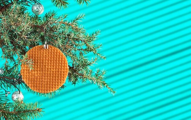 Festliche weihnachtskarte, banner oder postkarte mit zweig des weihnachtsbaumes mit zapfen und verziert mit waffel auf türkisfarbenem tisch, lichtstreifen von der sonne auf dem tisch, selektiver fokus
