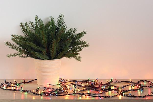 Festliche weihnachtskomposition mit einer elektrischen girlande und einem weihnachtsbaum auf dem tisch