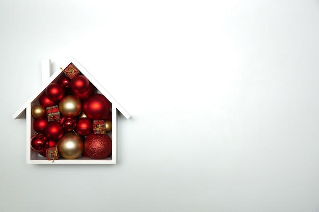 Festliche weihnachtskomposition mit haus und mit weihnachtskugeln. draufsicht
