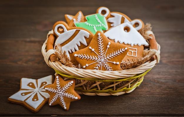 Festliche weihnachtslebkuchenplätzchen in form eines sternes liegen auf einem hölzernen dunkelbraunen hintergrund.