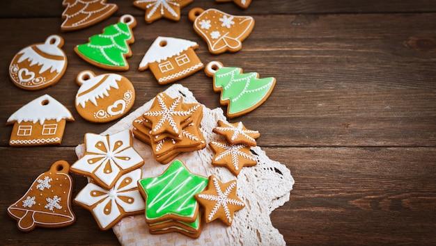 Festliche weihnachtslebkuchenplätzchen in form eines sternes liegen auf einem hölzernen dunkelbraunen.