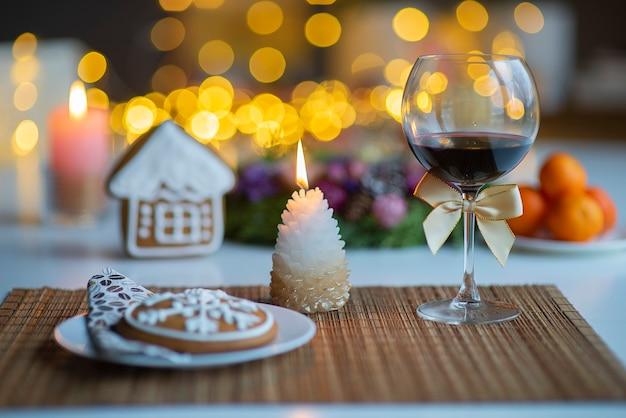 Festliche weihnachtsstimmung mit einem glas wein und einer brennenden kerze auf dem küchentisch