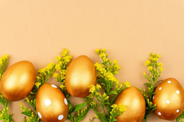 Festliche wohnung lag mit goldenen ostereiern und solidago-blumen auf braunem hintergrund