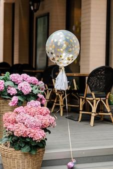 Festlicher ballon mit goldenem konfetti unter den blumentöpfen mit hortensien im restaurant. weicher selektiver fokus.