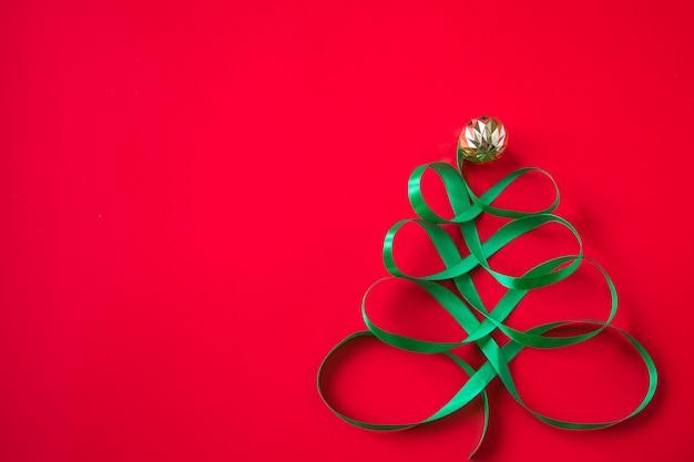 Festlicher baum aus satingrünem band auf rotem grund. kreatives weihnachtskonzept für werbung.