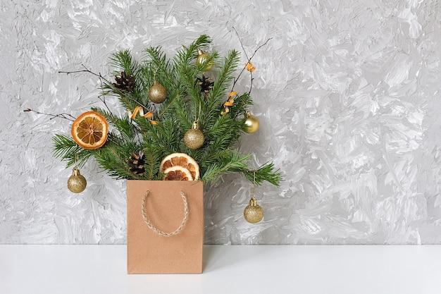 Festlicher blumenstrauß des winters von fichtenzweigen verzierte goldene bälle, kegel im handwerkspaket auf tabelle