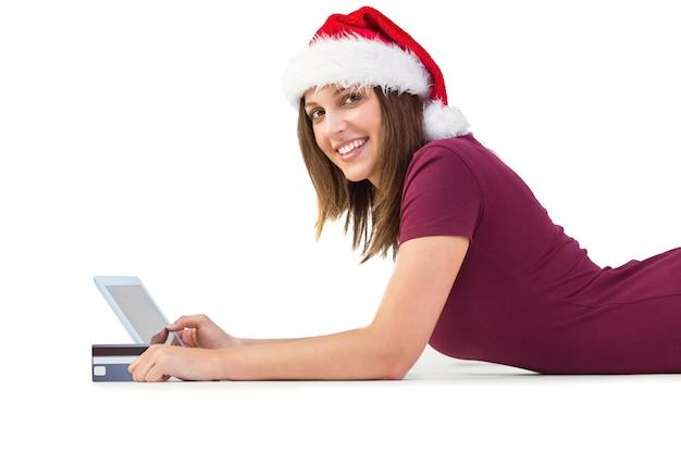 Festlicher brunette, der online mit tablette kauft