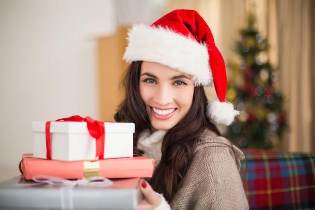 Festlicher brunette, der stapel der geschenke am weihnachten hält
