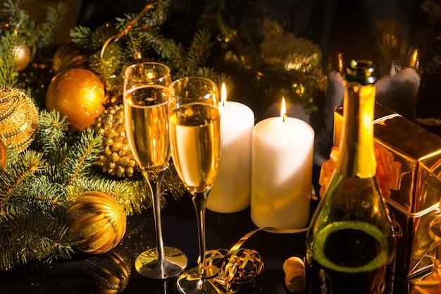 Festlicher champagner-weihnachtshintergrund mit kugeln, tannenzweigen, goldgeschenken, brennenden kerzen und einer flasche und gläsern romantischem champagner für zwei