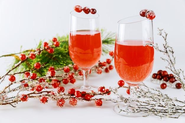 Festlicher cranberry-cocktail mit roter beerendekoration auf weißer oberfläche.
