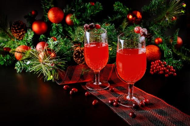 Festlicher cranberry-cocktail mit weihnachtsdekoration auf dunkler oberfläche. neujahrsgetränk.