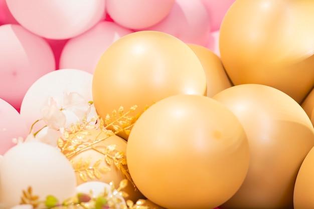 Festlicher dekorationsbereich mit großen goldenen und rosa luftballons blumen zum geburtstag, hochzeit, valentinstag
