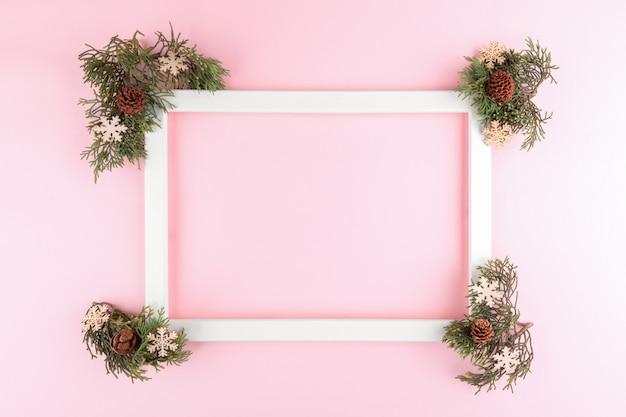 Festlicher eleganter hintergrund. leerer fotorahmen auf pastellrosa hintergrund mit tannenbaumzweigen. weihnachten