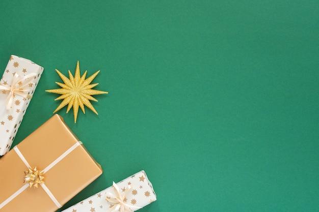 Festlicher grüner hintergrund mit golddekoration, hintergrund mit glitzergoldstern und geschenkboxen, flache lage, draufsicht, kopierraum