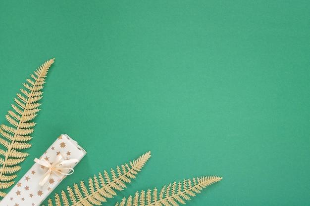 Festlicher grüner hintergrund mit golddekoration, hintergrund mit glitzernden goldenen farnblättern und geschenkboxen, flache lage, draufsicht, kopierraum