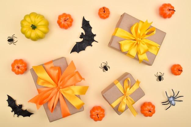 Festlicher halloween-hintergrund mit geschenken, kürbissen und spinnen auf beigem hintergrund. ansicht von oben. flach liegen.
