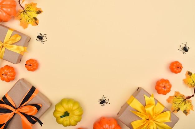 Festlicher halloween-hintergrund mit geschenken, kürbissen und spinnen.