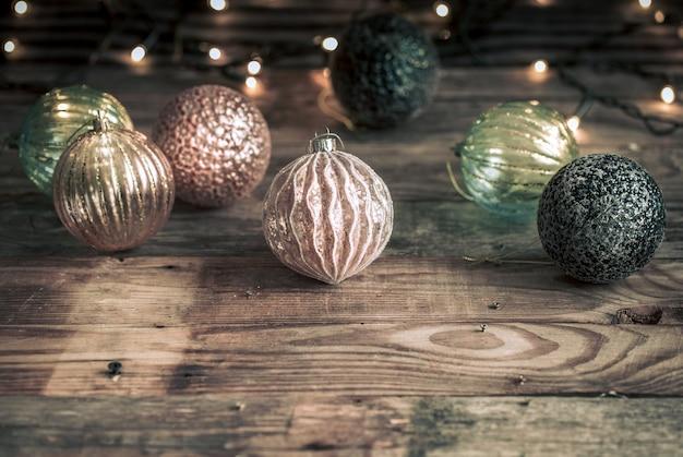 Festlicher hintergrund des weihnachts- oder neujahrs, weinlesespielzeug auf dem weihnachtsbaum auf einem hölzernen hintergrund mit einer girlande mit lichtern