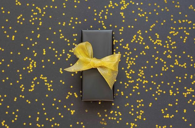 Festlicher hintergrund, geschenkbox mit glänzendem goldenem band auf schwarzem hintergrund mit glitzernden goldenen sternen, flache lage, draufsicht