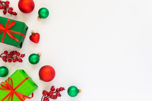 Festlicher hintergrund, geschenkboxen mit roten bändern und einem zweig weißdorn, christbaumkugeln und tannenzweigen auf weißem hintergrund, flache lage, draufsicht, kopienraum