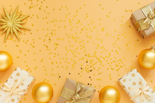 Festlicher hintergrund, geschenkboxen und weihnachtskugeln auf hintergrund mit glitzernden goldenen sternen, flache lage, draufsicht, kopienraum