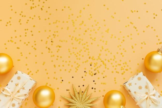 Festlicher hintergrund, geschenkboxen und weihnachtskugeln auf hintergrund mit goldenen glitzersternen, flache lage, draufsicht, kopierraum