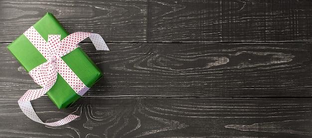 Festlicher hintergrund, horizontale fahne mit grüner geschenkbox und band auf einem braunen hölzernen hintergrund, valentinstag oder geburtstag, weihnachten