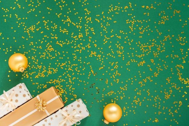 Festlicher hintergrund mit dekorationen, geschenkboxen und weihnachtskugeln auf grünem hintergrund mit glitzernden goldenen sternen
