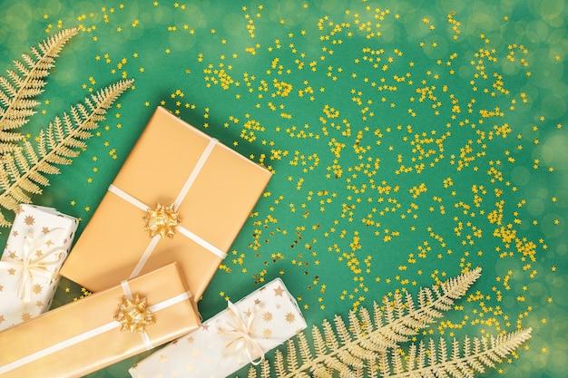 Festlicher hintergrund mit dekorationen, hell glänzenden goldenen farnblättern und geschenkboxen auf grünem hintergrund mit goldenen glitzersternen, flacher lage, draufsicht, kopierraum